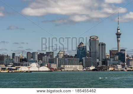 Auckland New Zealand - March 3 2017: City skyline seen from greenish ocean water under blue sky with some white clouds. Highrises Sky Tower and specific office buildings.