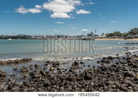 Auckland New Zealand - March 3 2017: City skyline with With commercial harbor and beyond seen over greenish ocean water under blue sky with some white clouds and shot from Devonport Beach.