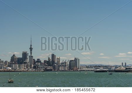 Auckland New Zealand - March 3 2017: City skyline with Westhaven and beyond seen over greenish ocean water under blue sky from Devonport boardwalk. Highrises Sky Tower airplane and boats.