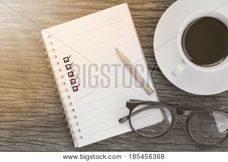 Note book with five check marks glasses a pencil and a cup of coffee on wooden background copy space. Background for anything.