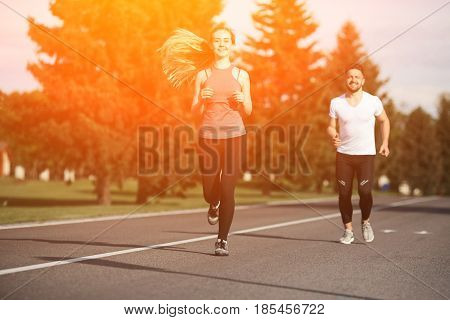 Closeup portrait of sport woman jogging along road with her partner or boyfriend running on background. Fitness, sport and lifestyle concepts. Toned.