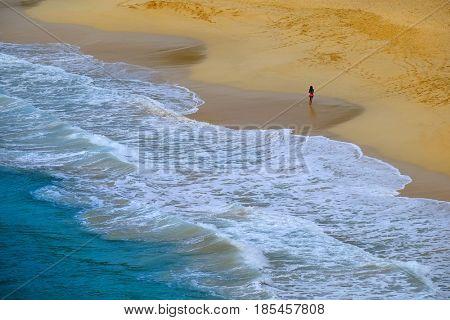 Bautiful beach rolling ocean waves and girl walking