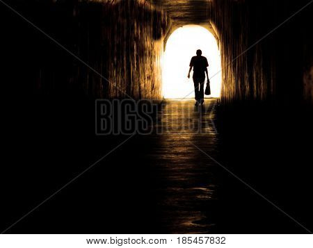 Old man walking through tunnel sihouetted