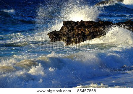 Ocean waves smashing and rolling over rocks on beach