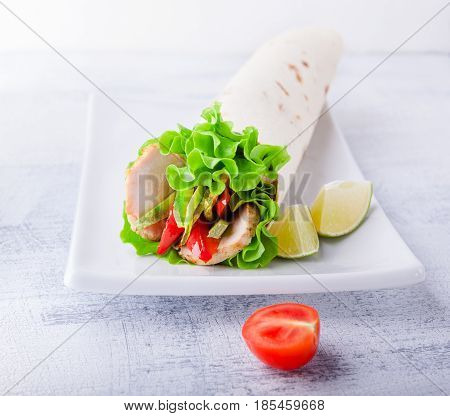 Sandwich wrap with garden salad, chicken, lettuce and tomato in a whole wheat tortilla