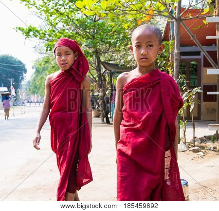 MINGUN MYANMAR-MARCH 6, 2017: Two unidentified young novice monks walking morning alms in Mingun, Myanmar on March 6, 2017.