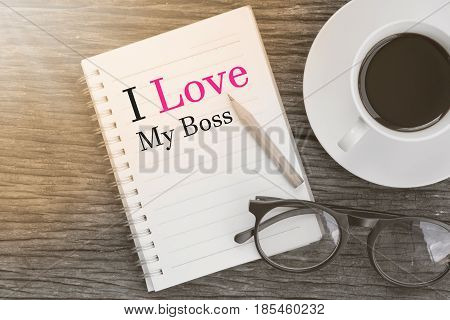 Concept I Love My Boss message on notebook with glasses pencil and coffee cup on wooden table.
