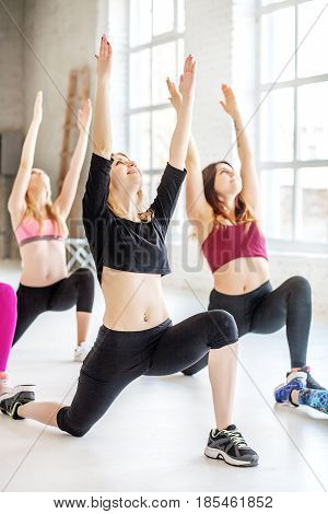 Young women practice yoga at the gym. The concept of sports dance yoga and healthy lifestyle.