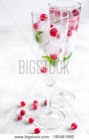 Ice cubes with fresh berries and mint in glasses for summer drink on white table background