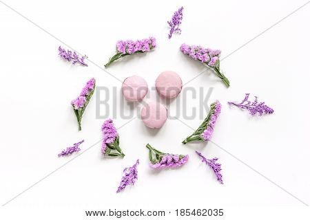 modern spring design in pastel color with macaroons and flowers on white background top view