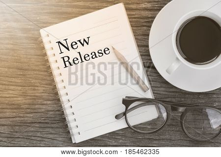 Concept New Release message on notebook with glasses pencil and coffee cup on wooden table.