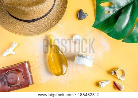 Summer cosmetic set for woman with protection cream and outfit on orange background top view