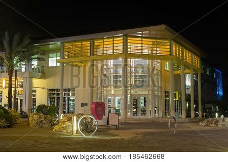 Illuminated glass bookstore building in a pedestrian street of a waterfront town on Grand Cayman