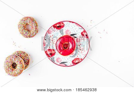 tasty lunch with colorful donuts on plate on white table background top view mock up