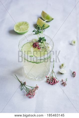 sweet fresh cocktail with flowers and cut lime for summer on stone desk background