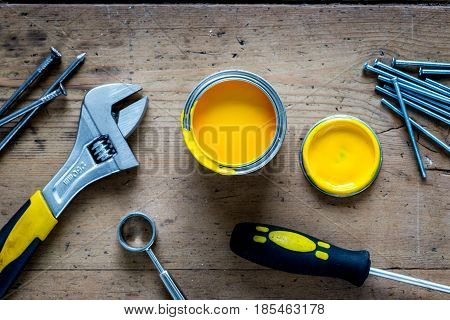 workplace of professional builder with instruments and paint set on wooden background top view