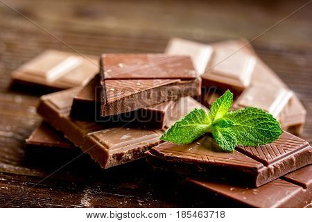 black and milk chocolate bars with mint on dark wooden table background