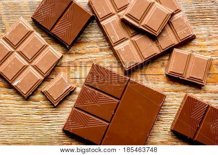 black and milk chocolate bars with mint on dark wooden table background top view