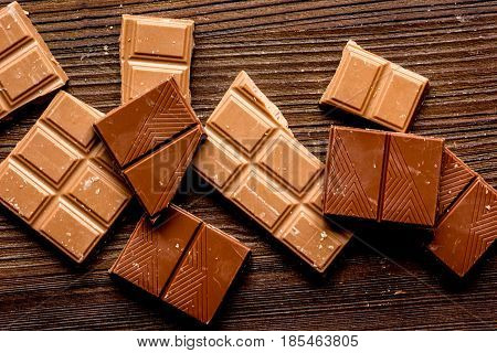 black and milk chocolate pieces on wooden table background top view