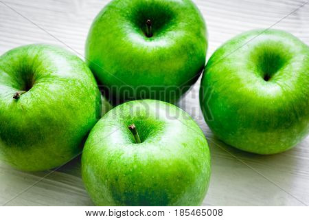 ripe green apples on white table background