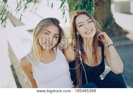 two girls sitting in the park and listen to music with headphones