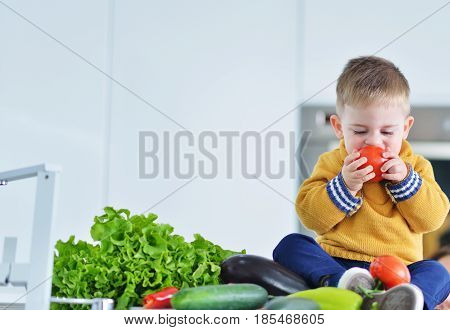 kid boy eating healthy vegetables at kitchen.