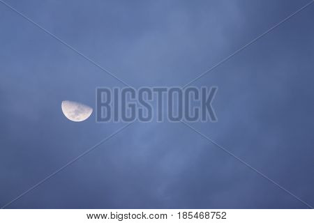 Half moon on dark sky with moving cloud.