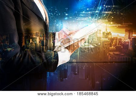 Businessman with tablet on futuristic background with city. The technology that develops in the future