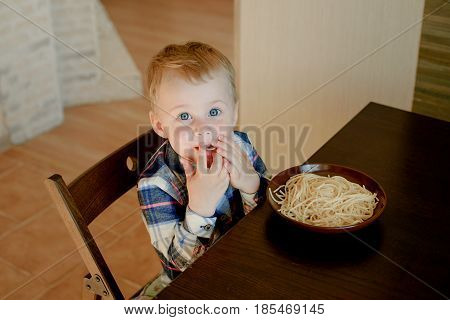 A cheerful boy of two years eating spaghetti with his hands at home