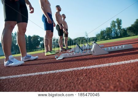 Male athletics runners on starting line without shirts