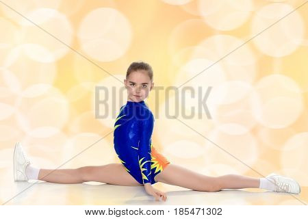 A beautiful girl gymnast of school age, in a beautiful blue training suit makes a twine.Turn the camera to the side.