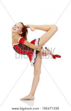Cute little girl gymnast in a beautiful costume for competition, performs exercises with mace.Isolated on white background.