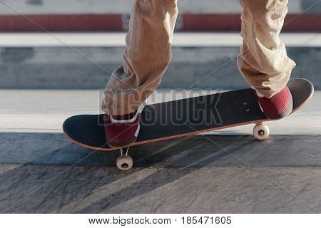 A skateboarder and skateboard on the edge