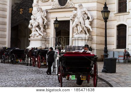 VIENNA-MARCH 30 2017. Coachman sitting in the carriage awaiting for tourists for excursion near Hofburg. March 30 2017 Vienna Austria.