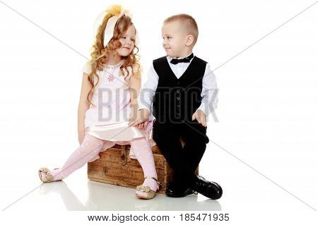 Little boy and girl sitting on the old trunk.Isolated on white background.