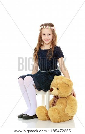 Beautiful little girl in a blue dress, holding in his paw a big Teddy bear.Isolated on white background.