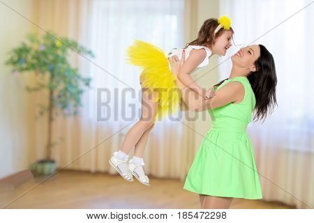 Beautiful young mother in a short green dress and her little beloved daughter in a yellow skirt.Fun mother throws daughter on hands.Turning sideways to the camera.In the children's room.