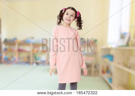 Cute little girl with long curly tails on the head, in which braided red ribbons . In long pink dress. Baby girl cute smiling standing in front of the camera.In the Montessori room the children's garden .