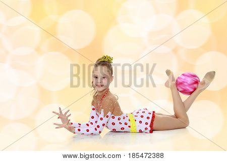 Beautiful little girl gymnast dressed in sports suits for competition, performs exercises with the ball.Brown festive, Christmas background with white snowflakes, circles.
