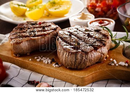 Grilled beefsteaks on cutting board - dinner preparation