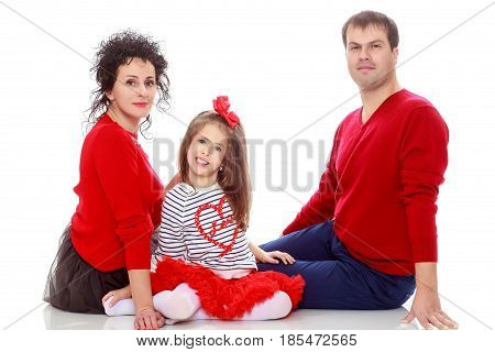 Happy young family dad mom and a little girl in bright red outfits . Dad holds daughter on hands.Isolated on white background.
