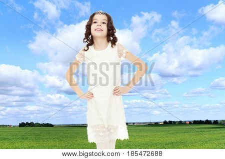 Cute little girl with long, dark curly hair , in a long white beautiful dress. Girl holding hands on the belt. Close-up.On the background of green grass and blue sky with clouds.