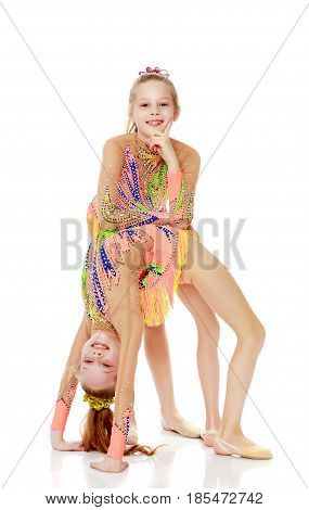 Two little twin girls who are doing gymnastics, doing the bridge.Isolated on white background.