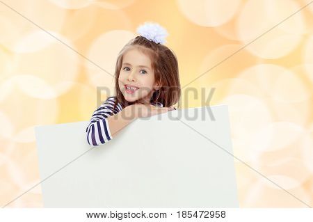 The little blonde girl with long hair and with a white bow on her head , in a blue striped summer dress.She peeks out from behind white banner.