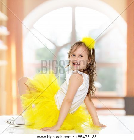 Joyful little blonde girl in a short yellow skirt and yellow bow on her head.She's sitting on the floor turning her back to the camera and laughs.In a room with a large semi-circular window.
