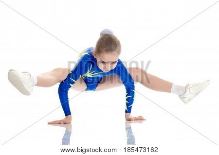 A charming gymnast girl, a younger school age, in a beautiful blue swimsuit, performs an exercise on the floor.She makes a stand on her hands, and performs a twine.