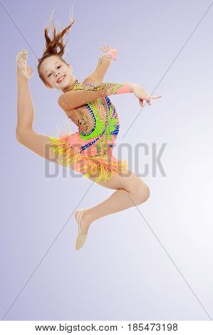 Beautiful little girl gymnast dressed in sports swimsuit for competitions, performs a jump.On a light purple gradient background.