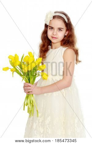 A nice little school-age girl in a smart white dress.With a bouquet of tulips in hands.
