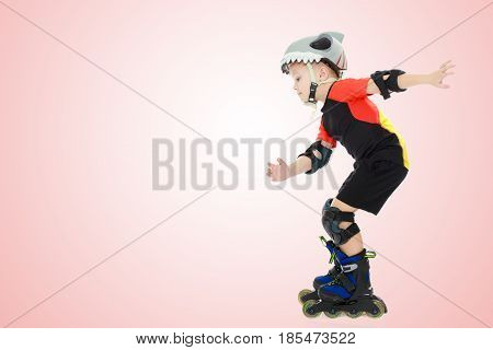 Sports little boy riding on roller skates helmet and knee pads. Side view.Pale pink gradient background.