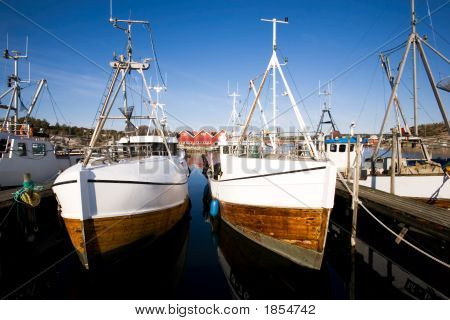 A number of fishing boats sit at dock on a warm summer day. poster